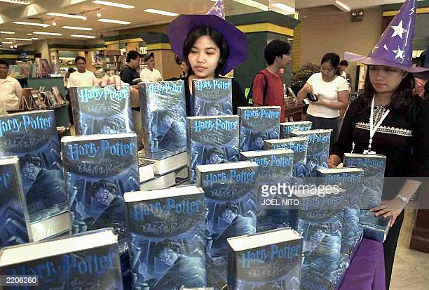 Salesgirls wearing witch hats display copies of the latest Harry Potter book 'Harry Potter and the Order of the Phoenix' being snapped up in...