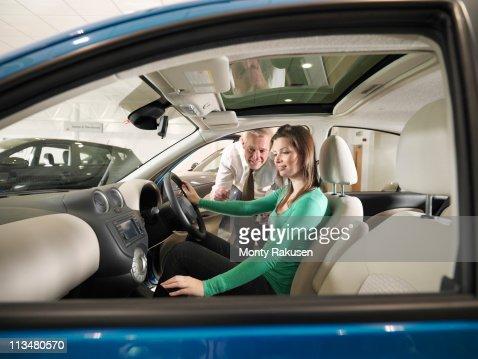 Salesman advises female customer who is sat in car in car dealership