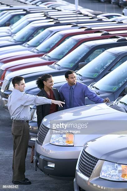 Salesman and couple car shopping