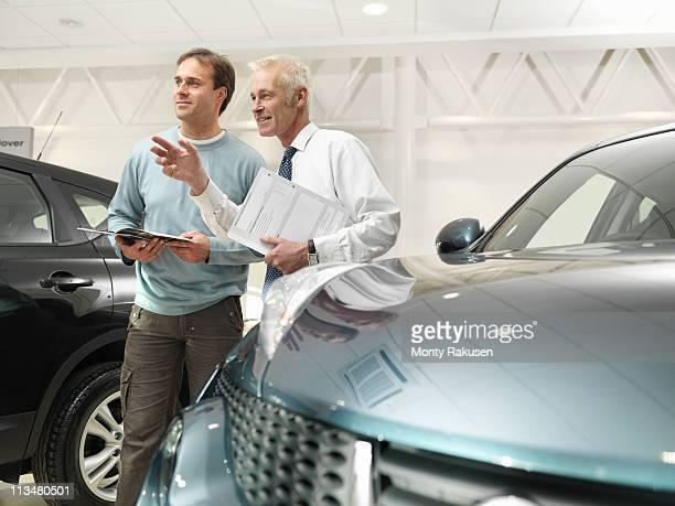 Salesman and customer in car dealership