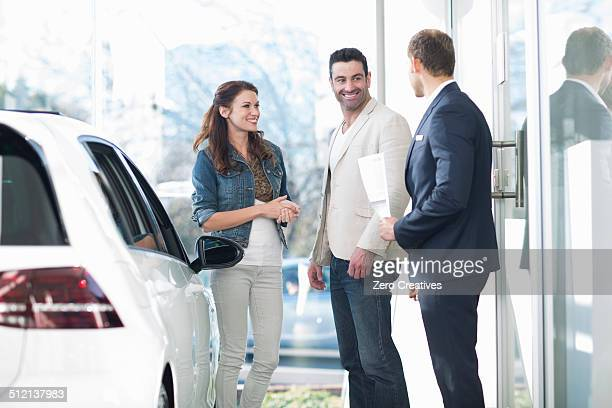 Salesman and mid adult couple chatting in car dealership