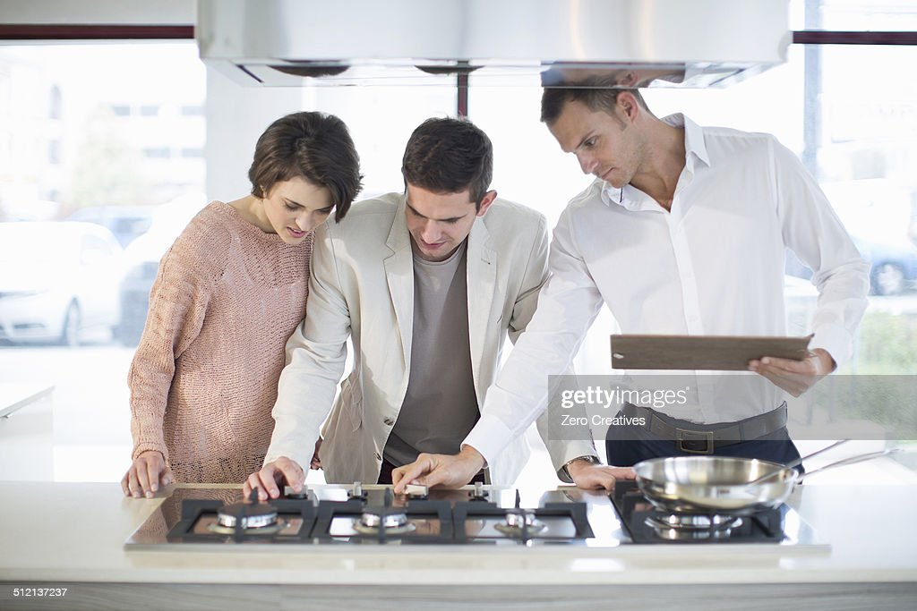 Salesman and mid adult couple looking at hob in kitchen showroom