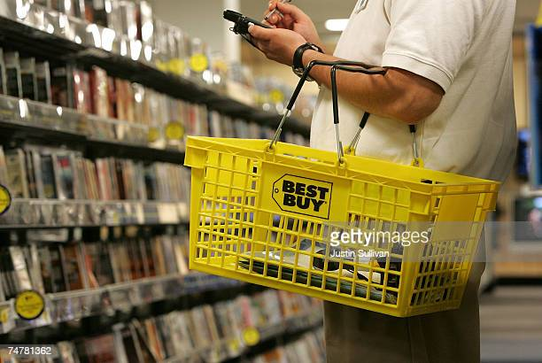 A salesman carries a Best Buy shopping basket as he takes inventory of DVD movies at a Best Buy store June 19 2007 in San Francisco California...