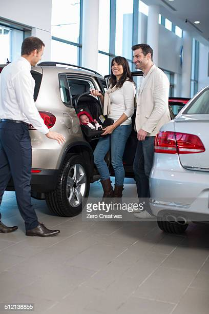 Salesman chatting to family with baby girl in car dealership
