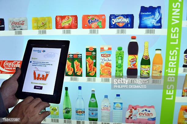 A salesman demontrates shopping with a tablet computer as customers can shop with their smartphone after downloading the mobile application 'My...