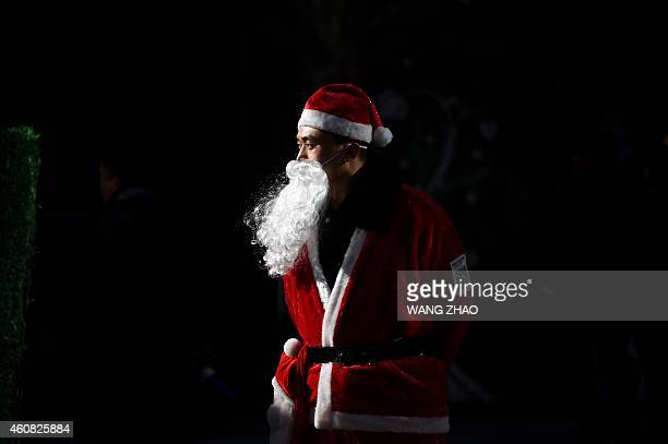 A salesman dressed as Santa Claus waits for customers at the entrance of a shop in Beijing on December 25 2014 Christmas once banned in China has...