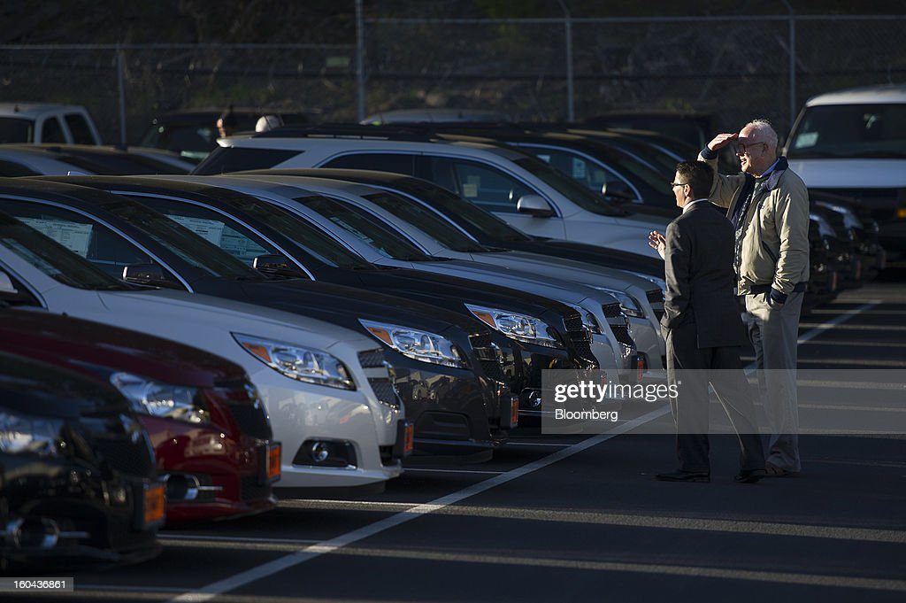 Salesman Drew Price left helps a customer at Stewart Chevrolet Cadillac dealership in Colma California US on Wednesday Jan 30 2013 US auto...