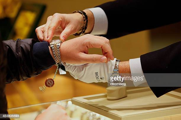 A salesman fits a Rolex Group watch to a customer at the GEARYS Rodeo Drive Rolex store in Beverly Hills California US on Monday Dec 9 2013 Consensus...