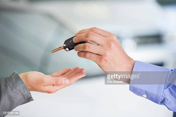 Salesman handing car key to woman