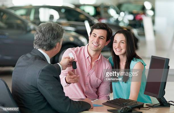 Salesman handing car keys to smiling couple at desk in car dealership showroom