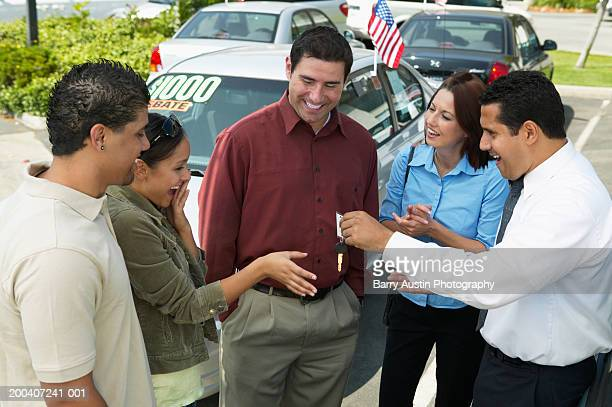 Salesman handing car keys to young woman with parents, smiling