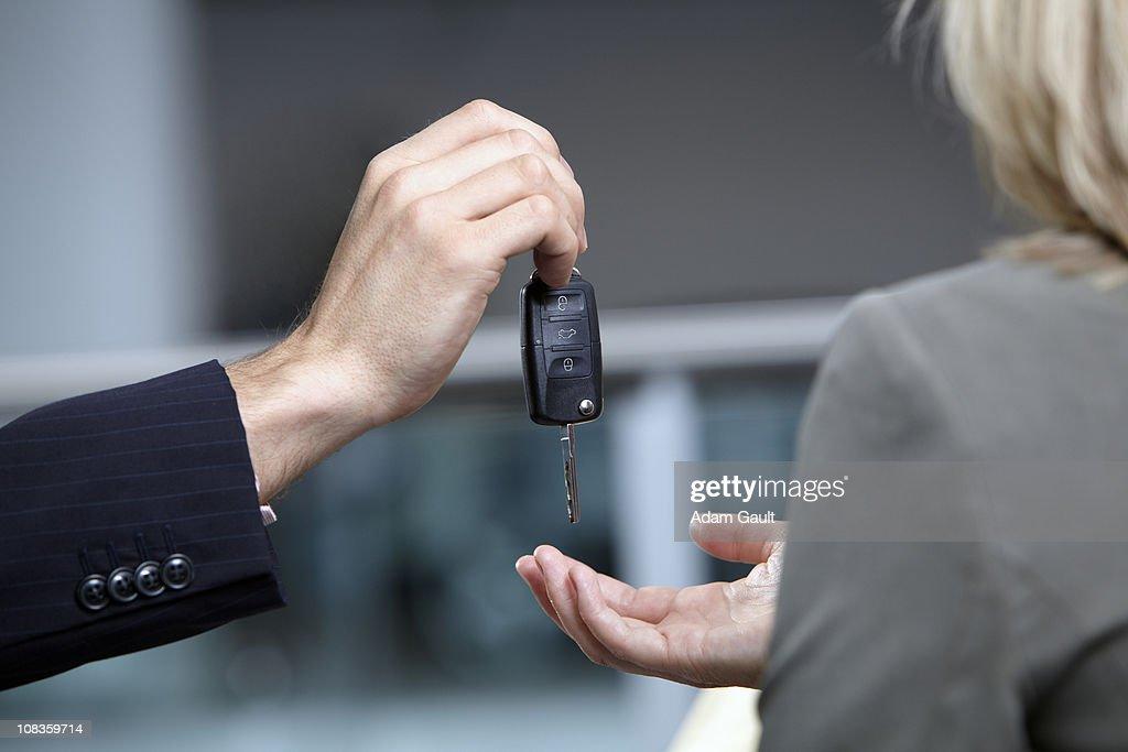 Salesman handing woman car keys in automobile showroom