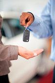 Salesman handing woman new car keys