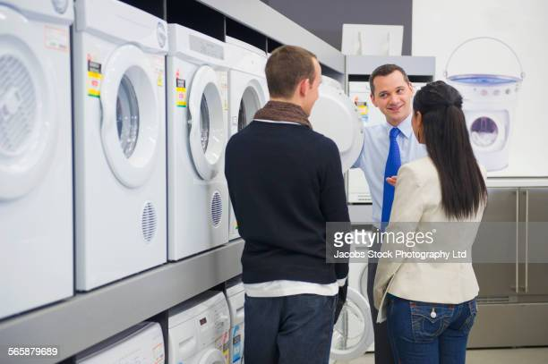 Salesman helping couple shopping for washing machine in store
