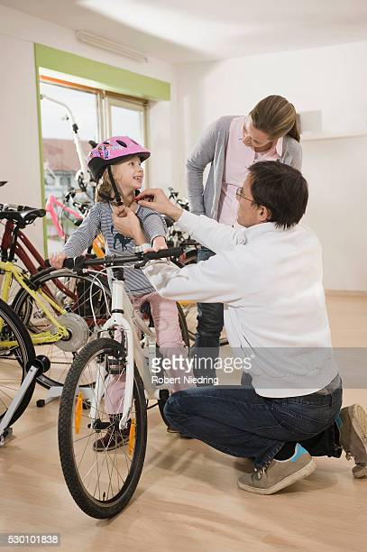 Salesman helping girl to wear cycling helmet