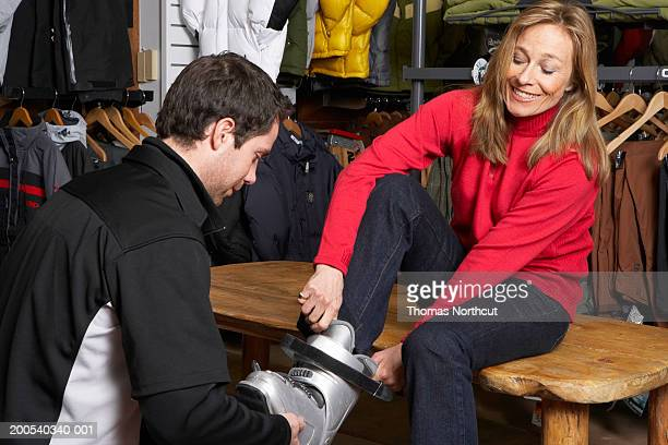 Salesman helping mature woman try on ski boots in sports shop
