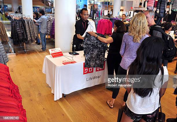 A salesman helps customers with their purchases at the Uniqlo Japaneseowned casual wear retail store in San Francisco's Union Square shopping district