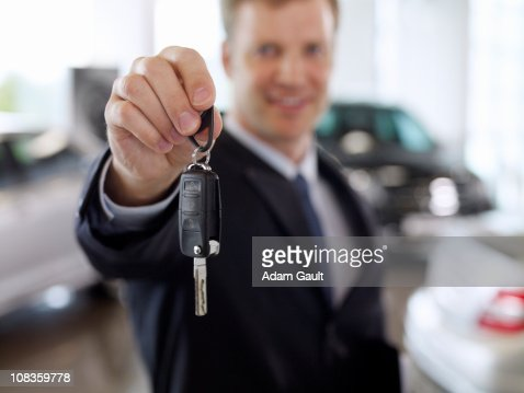 Salesman holding out car key in automobile showroom : Stock Photo