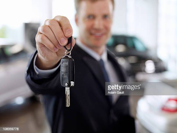 Salesman holding out car key in automobile showroom