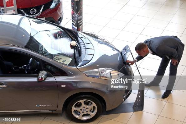 A salesman inspects the charging point of a new new Nissan Leaf electric automobile produced by Nissan Motor Co as it stands for sale at Toomey Motor...