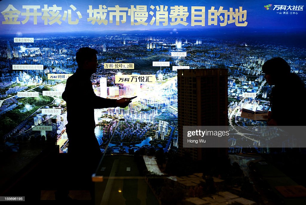 A salesman introduces the houses for a consumer in fornt of a real estate poster at a shopping mall on November 6, 2012 in Chongqing, China.
