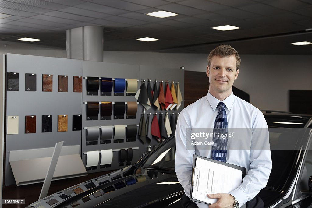 Salesman leaning in new car in showroom : Stock Photo