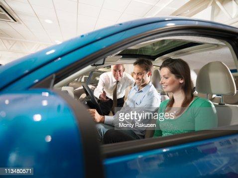 Salesman leaning through window of car, advises customers sat in car, in car dealership