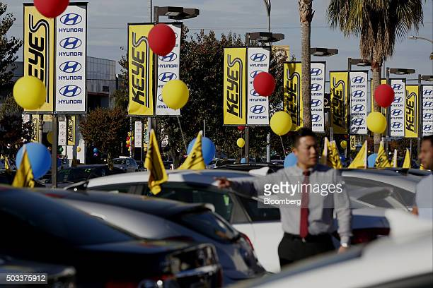 A salesman left points to a vehicle on the lot of the Keyes Hyundai Motor Co dealership in the Van Nuys neighborhood of Los Angeles California US on...