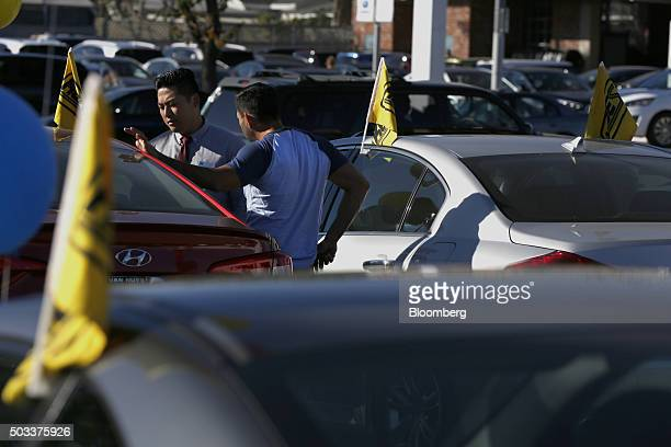 A salesman left speaks to a potential car buyer while viewing a Hyundai Motor Co vehicle on the lot of the Keyes Hyundai dealership in the Van Nuys...