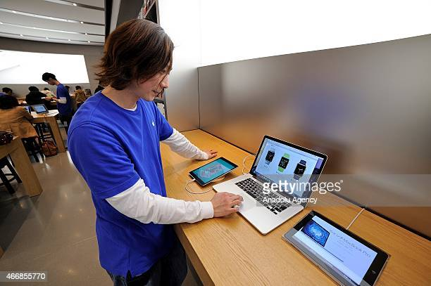 A salesman looks at the new apple device on a Macbook in the Apple store at the highend shopping district of Omotesando in Tokyo Japan on March 19...
