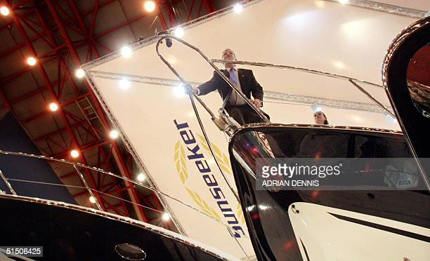 A salesman looks over the bow of a luxury motor yacht at the London Boat Show at Earls Court arena 04 January 2001 The show features 800 boats on...