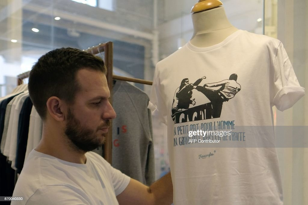 A salesman places a parodic t-shirt reading 'A small step for the man, a giant step towards retirement' (Un petit Pat pour l'homme, un grand Pat pour la retraite) on a plastic dummy in Marseille on November 4, 2017. A Marseille clothing designer is hoping to make hay with a hastily-designed t-shirt mocking Patrice Evra's karate kick on one of his team's own fans. The caption, a play on words with 'Pat' and 'pas' (step) evokes American astronaut Neil Armstrong's iconic message back to earth when he became the first man to step on the moon in 1969. /