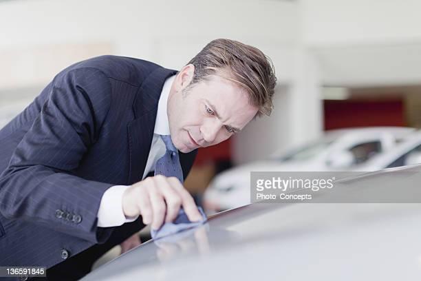 Verkäufer Polieren Auto mit seiner Krawatte