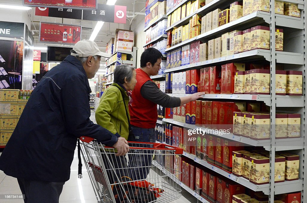 A salesman promotes white spirit products to a couple at a supermarket in Beijing on November 20, 2012. China Alcoholic Drinks Association said all Chinese 'White spirit' had plasticizer. AFP PHOTO WANG ZHAO
