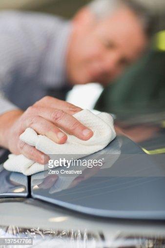 Salesman shining car in showroom
