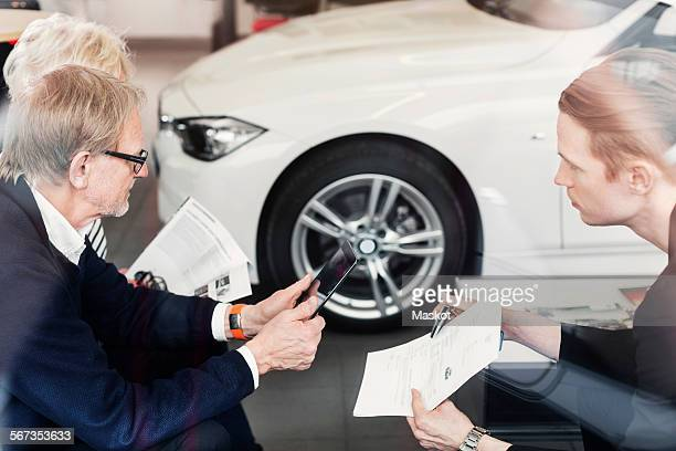 Salesman showing agreement to senior couple in car dealership
