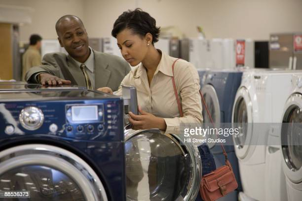 Salesman showing customer washing machine in showroom