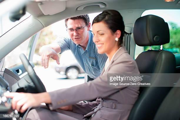 Salesman showing woman new car