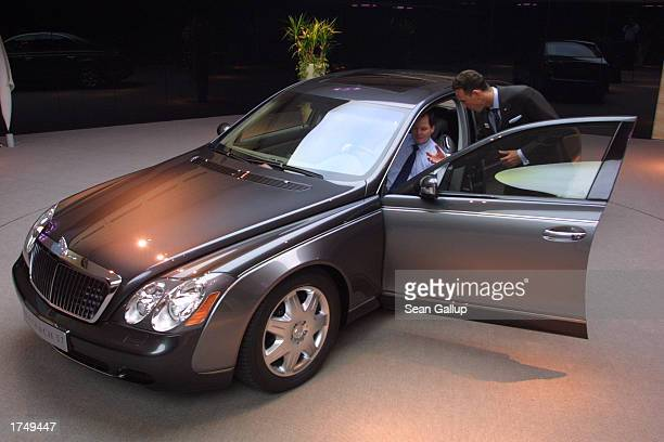 A salesman shows a potential customer details of a Maybach 57 limousine which retails for EUR 359 approximately $390 sits at a Maybach dealership...