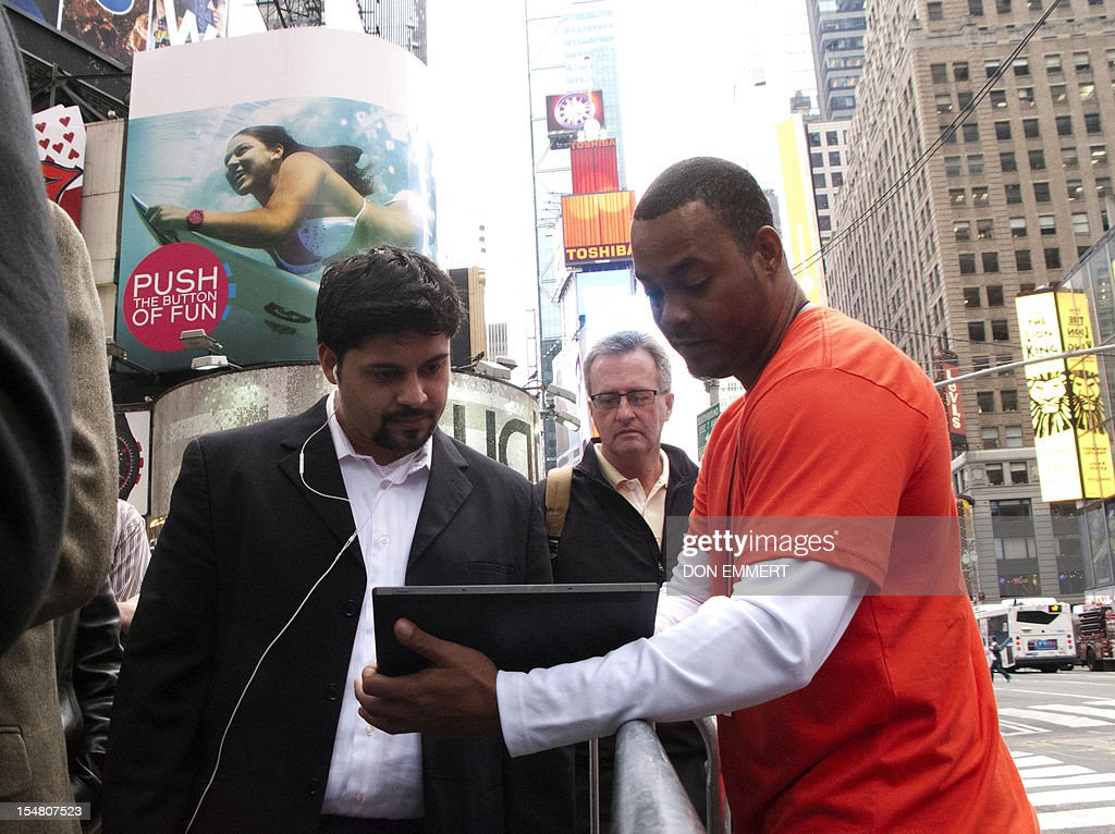 A salesman (R) shows off a Microsoft Surface outside Microsoft's pop-up store, set up on the corner of 46th Street in Times Square to mark the release of its Surface tablet, October 26, 2012 in New York. The store is one of more than 30 stores around the US showing off the Microsoft Surface and the new Windows 8 operating system.
