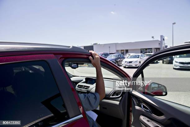 A salesman sits in the passenger seat of a vehicle while talking with a shopper at a Fiat Chrysler Automobiles car dealership in Moline Illinois US...
