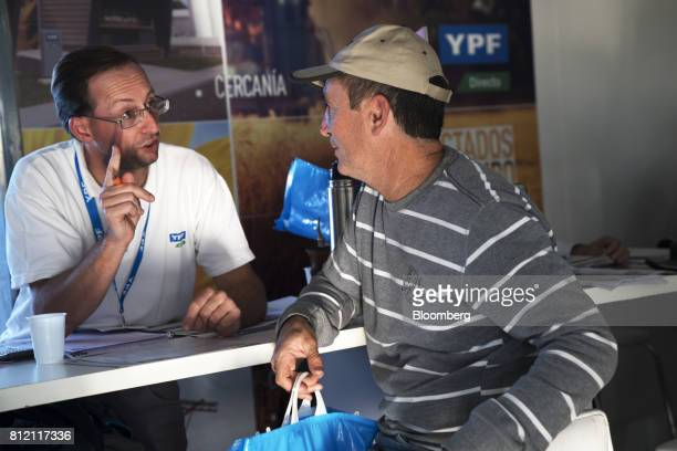SA salesman speaks to an attendee at the company's booth inside the AgroActiva fair in Armstrong Santa Fe Argentina on Thursday June 1 2017 YPF SA...