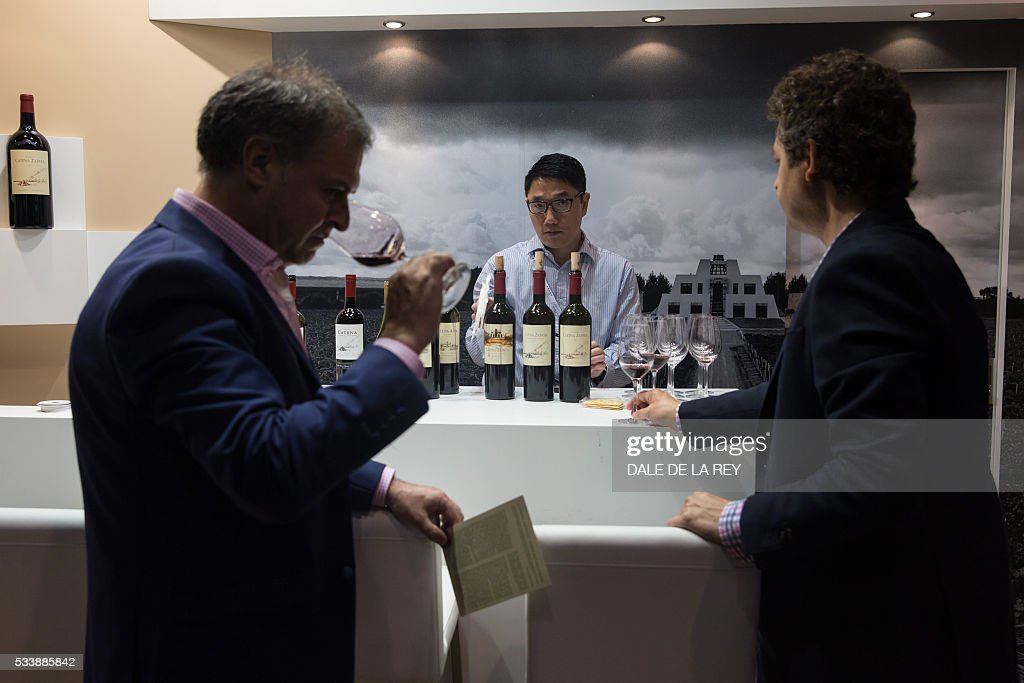 A salesman (C) speaks with customers during Vinexpo in Hong Kong on May 24, 2016. The international wine and spirits exhibition runs from May 24 to 26. / AFP / DALE
