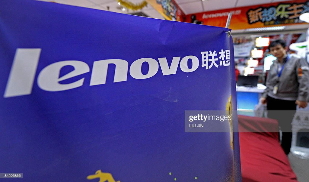 A salesman stands next to a banner displaying Lenovo's logo at its booth in a shopping mall in Beijing on January 8 2009 Chinese computer giant...