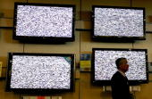A salesman stands next to display of flat screened television at a Best Buy store April 15 2009 in San Francisco California California state...