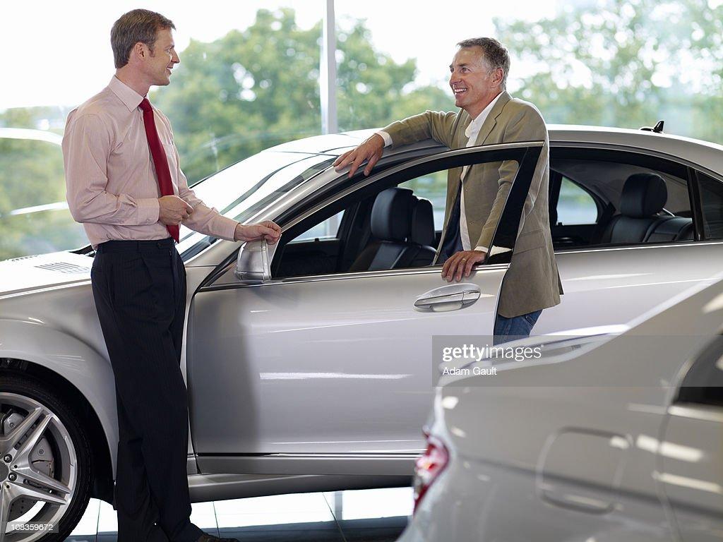 Salesman talking man in automobile showroom : Stock Photo