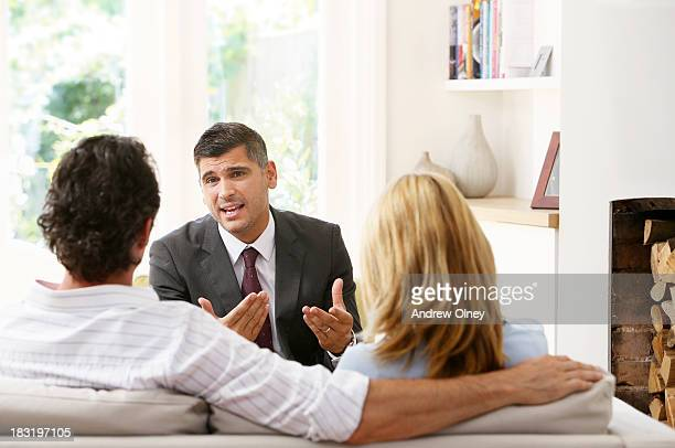 Salesman talking to a couple at home