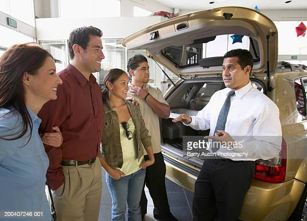 Salesman talking to family in car showroom, smiling
