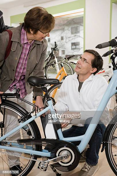 Salesman talking to woman beside bicycle