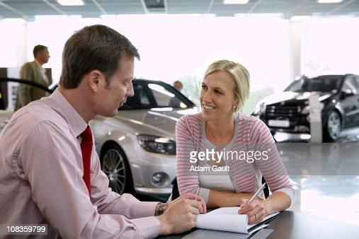 Salesman talking to woman in automobile showroom : Stock Photo